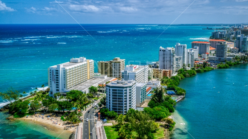 Hotels and high-rises on the coast, and crystal blue water, San Juan, Puerto Rico  Aerial Stock Photos | AX102_002.0000000F
