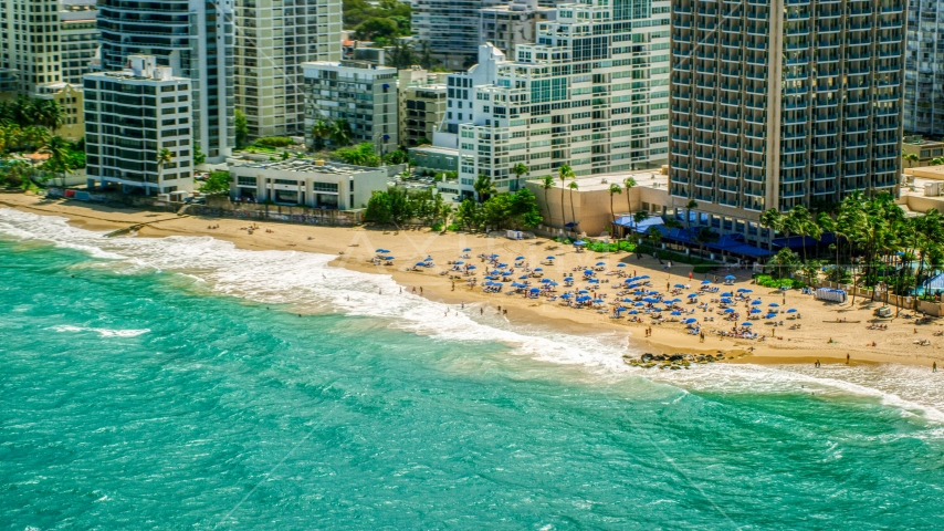 Tourists on a beach enjoying clear blue waters, San Juan, Puerto Rico Aerial Stock Photos | AX102_004.0000000F