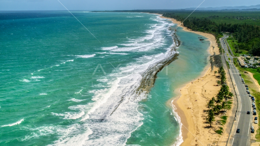Waves rolling toward the beach and highway, Loiza, Puerto Rico Aerial Stock Photos | AX102_018.0000143F