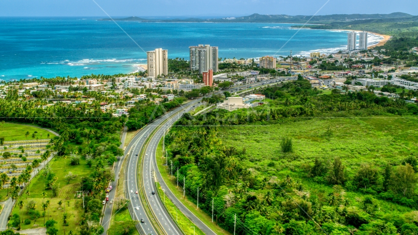 Beachside community and condos by crystal blue waters, Luquillo, Puerto Rico Aerial Stock Photos | AX102_049.0000000F