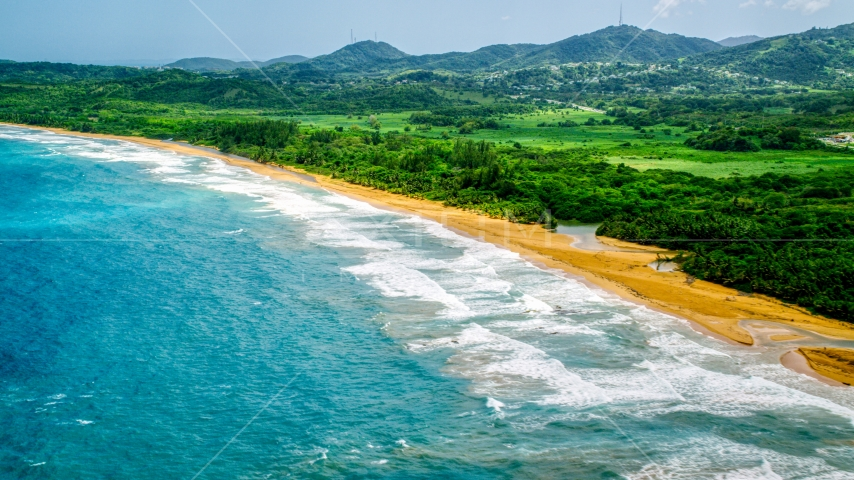 Ocean waves rolling toward an empty beach in Luquillo, Puerto Rico Aerial Stock Photos | AX102_051.0000227F