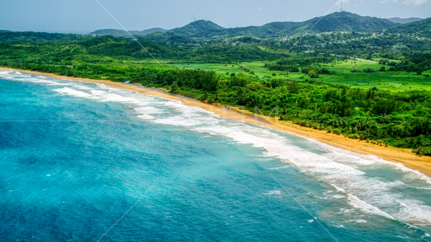 Waves rolling toward an empty beach and jungle in Luquillo, Puerto Rico  Aerial Stock Photos | AX102_052.0000138F