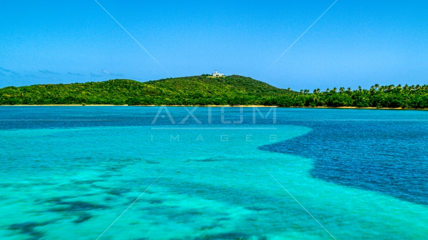 A view across crystal clear blue water of Cape San Juan Light, Puerto Rico Aerial Stock Photo AX102_060.0000000F | Axiom Images