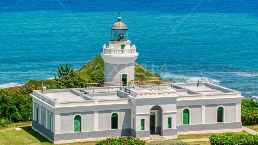 Cape San Juan Light looking out on to crystal blue waters, Puerto Rico Aerial Stock Photo AX102_066.0000000F | Axiom Images