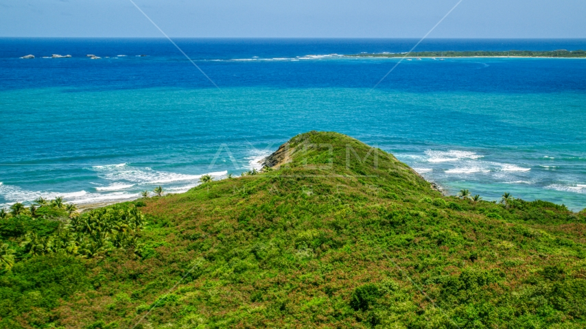 Green shore overlooking Caribbean ocean and tiny islands in Fajardo, Puerto Rico  Aerial Stock Photos | AX102_071.0000000F