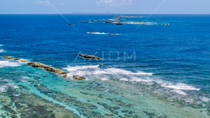 Rocks and waves in tropical blue waters, Puerto Rico  Aerial Stock Photos | AX102_084.0000239F