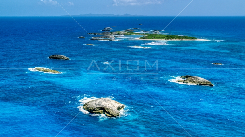 Tiny green Caribbean island in tropical blue waters, and smaller rocky islands, Puerto Rico  Aerial Stock Photos | AX102_088.0000024F