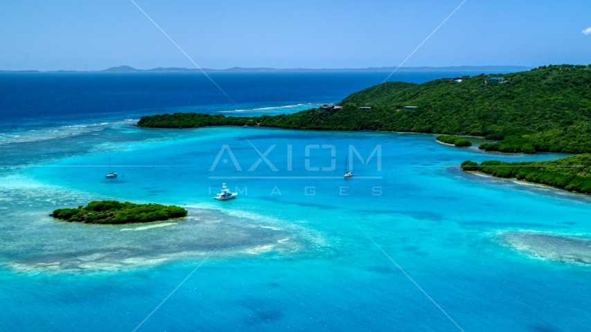 Fishing boat and sailboats in turquoise blue waters along the island coast, Culebra, Puerto Rico  Aerial Stock Photos | AX102_136.0000000F