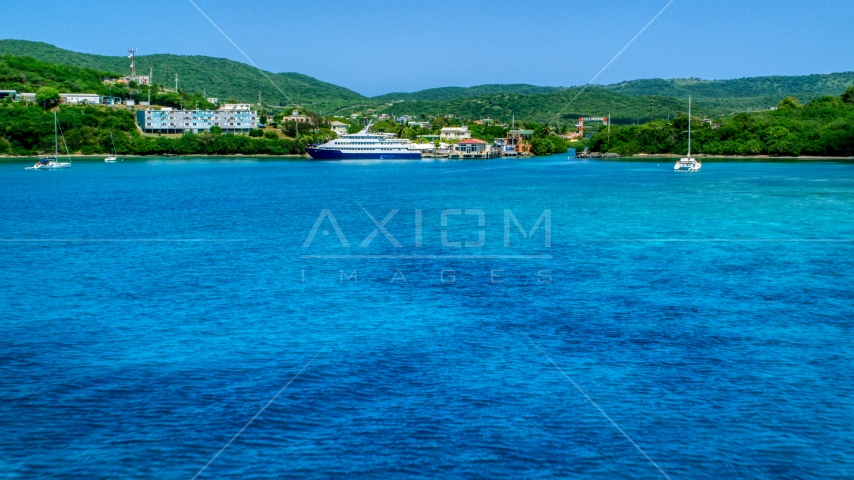 Ferry across a sapphire blue bay in Culebra, Puerto Rico  Aerial Stock Photos | AX102_148.0000239F
