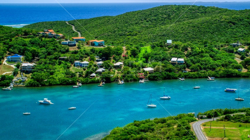Oceanfront island homes by boats in sapphire waters, Culebra, Puerto Rico Aerial Stock Photo AX102_155.0000201F | Axiom Images