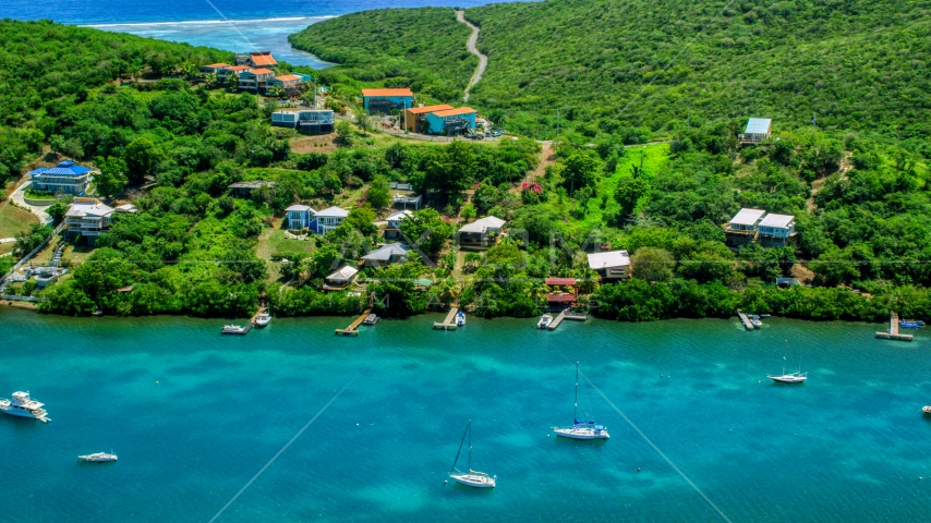 Island homes overlooking boats in the water in Culebra, Puerto Rico Aerial Stock Photos | AX102_156.0000000F