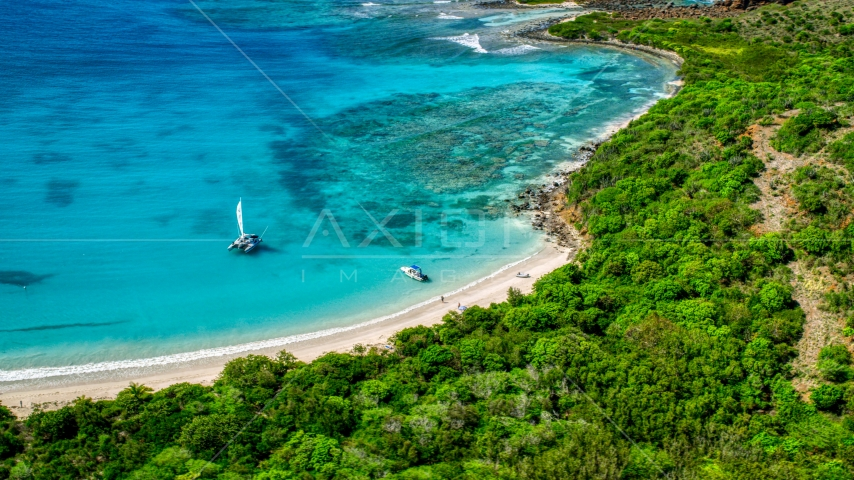 Pair of boats beside a white sand beach on the Caribbean island of Culebrita, Puerto Rico  Aerial Stock Photos | AX102_180.0000255F