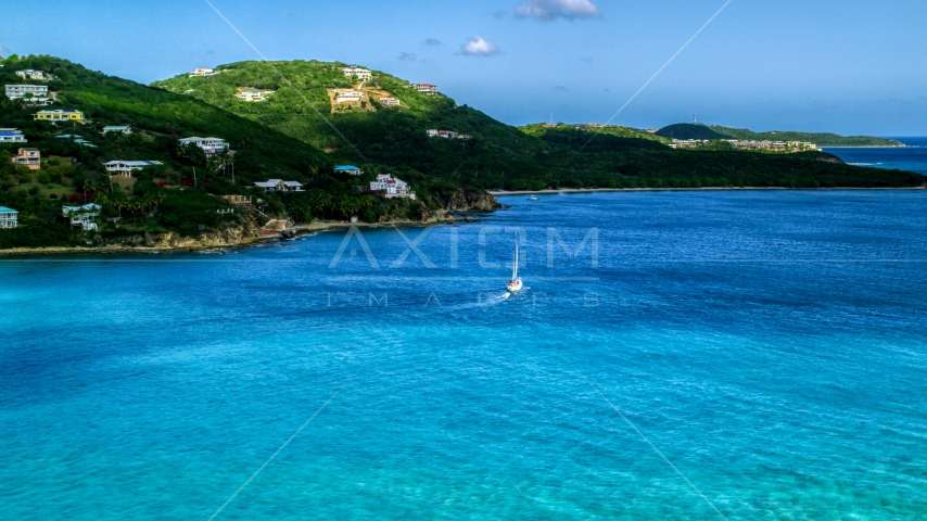 A sailboat near the Caribbean island coast with upscale homes, Southside, St Thomas  Aerial Stock Photos | AX102_234.0000000F