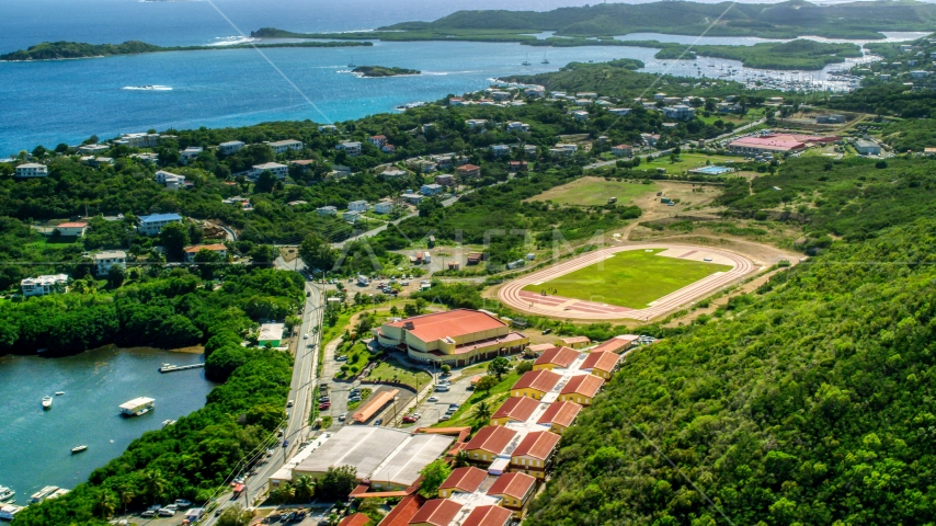 Island high school and track field near waterfront homes in East End, St Thomas, US Virgin Islands   Aerial Stock Photos | AX102_244.0000000F