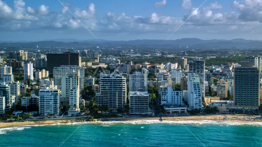 Beachfront condo complexes along Caribbean blue waters, San Juan, Puerto Rico Aerial Stock Photos | AX103_150.0000114F