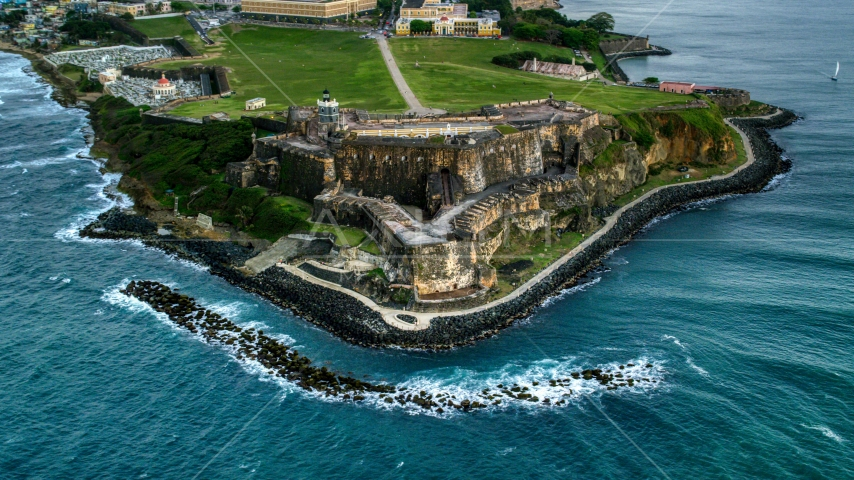 A view of Fort San Felipe del Morro along Caribbean blue waters, Old San Juan, twilight Aerial Stock Photos | AX104_084.0000000F