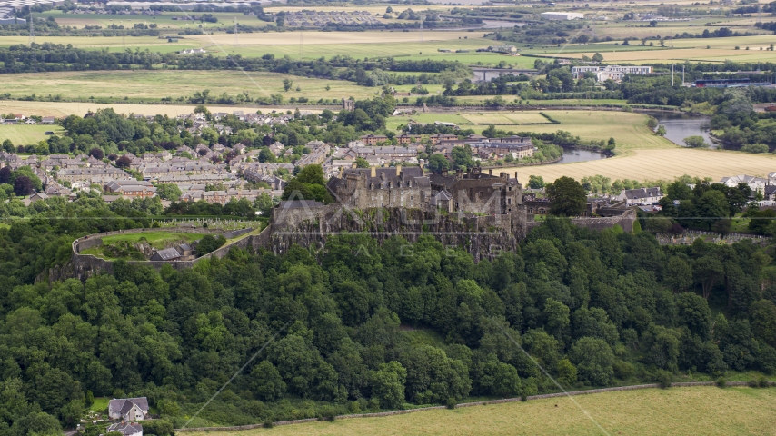 A view of hilltop Stirling Castle among trees, Scotland Aerial Stock Photos | AX109_019.0000084F