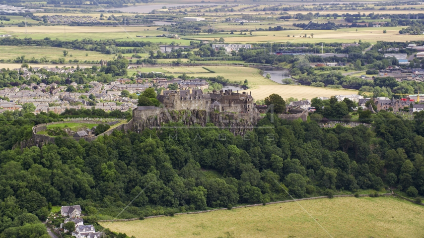 Historic Stirling Castle atop a tree-covered hill in Scotland Aerial Stock Photos | AX109_020.0000000F