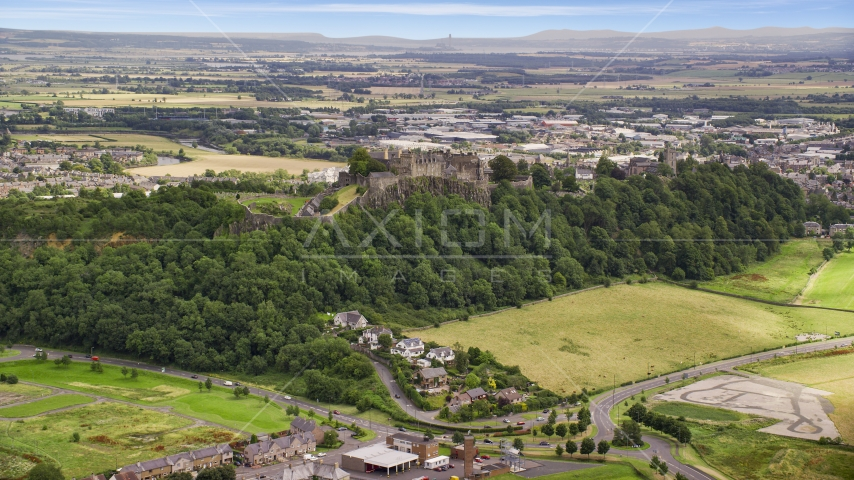 Iconic Stirling Castle among tree covered hillside, Scotland Aerial Stock Photos | AX109_022.0000000F