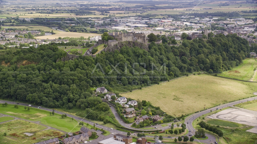 Historic Stirling Castle sitting atop a tree covered hillside, Scotland Aerial Stock Photos | AX109_022.0000135F