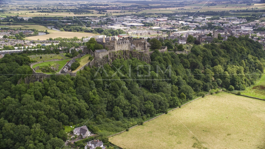 The historic Stirling Castle on a tree covered hill, Scotland Aerial Stock Photos | AX109_024.0000000F