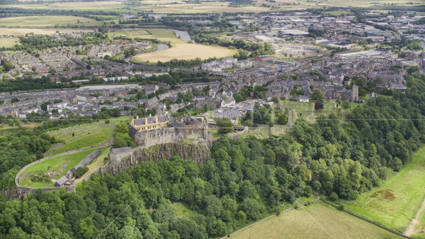 Stirling Castle on a tree covered hill, Scotland Aerial Stock Photos | AX109_037.0000000F