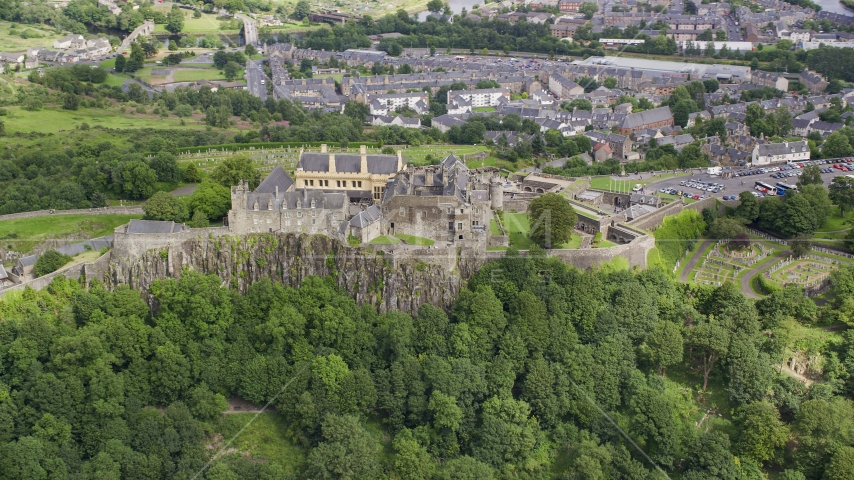 Stirling Castle atop a hill covered with trees, Scotland Aerial Stock Photos | AX109_038.0000000F