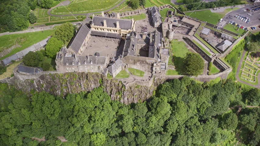 Iconic Stirling Castle and a tree covered hillside, Scotland Aerial Stock Photos | AX109_043.0000155F