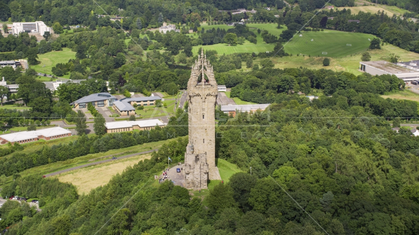 The historic Wallace Monument on a tree-covered hill, Stirling, Scotland Aerial Stock Photos | AX109_049.0000000F