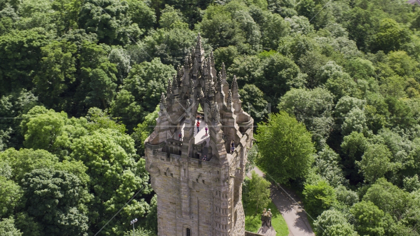 The top of historic Wallace Monument among trees, Stirling, Scotland Aerial Stock Photos | AX109_052.0000016F