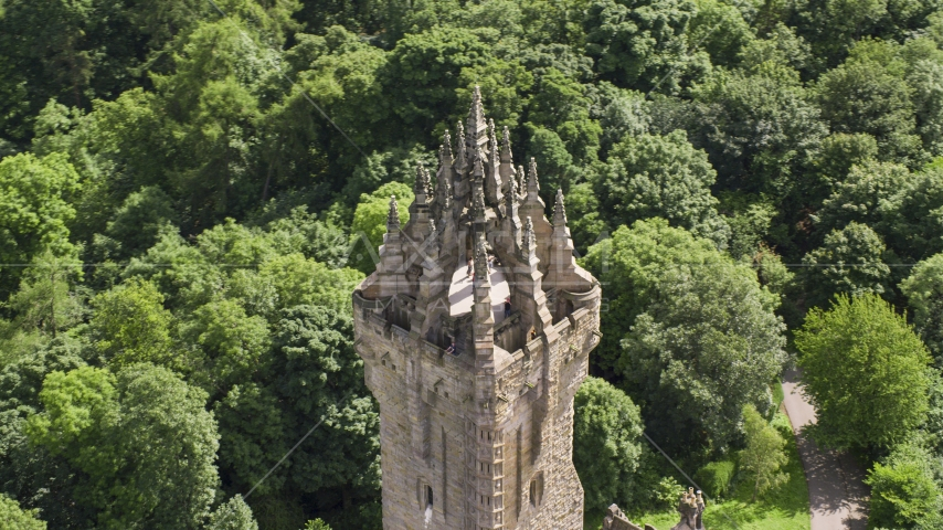 Top of iconic Wallace Monument near trees, Stirling, Scotland Aerial Stock Photos | AX109_052.0000110F