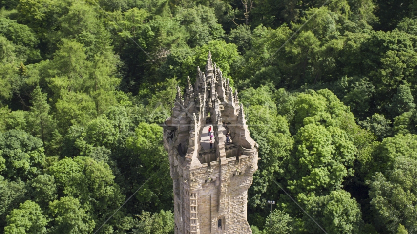 The top of iconic Wallace Monument with tourists, surrounded by trees, Stirling, Scotland Aerial Stock Photos | AX109_053.0000000F