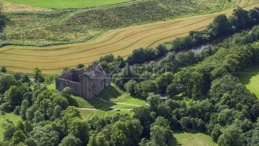 Historic Doune Castle beside a river in Scotland Aerial Stock Photos | AX109_066.0000137F