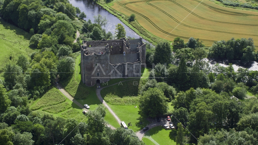 Iconic Doune Castle beside a river, Scotland Aerial Stock Photos | AX109_068.0000000F
