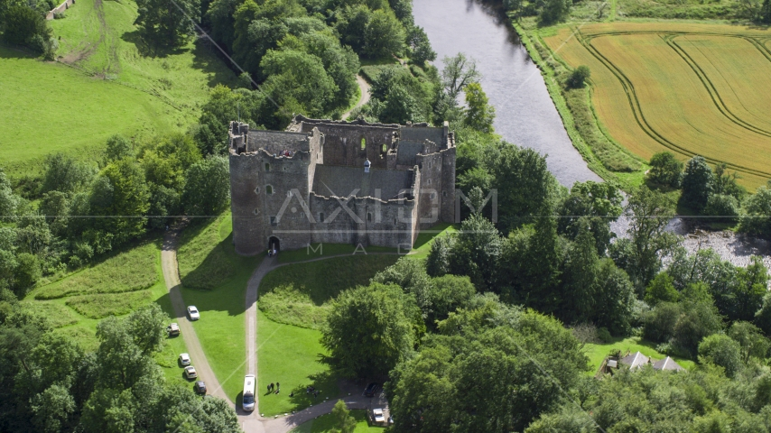 Historic Doune Castle beside a river, Scotland Aerial Stock Photos | AX109_068.0000123F