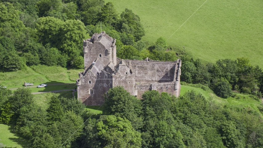 Iconic Doune Castle nestled in trees, Scotland Aerial Stock Photos | AX109_070.0000000F