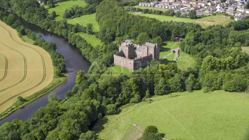The iconic Doune Castle with trees along a river, Scotland Aerial Stock Photos | AX109_074.0000000F
