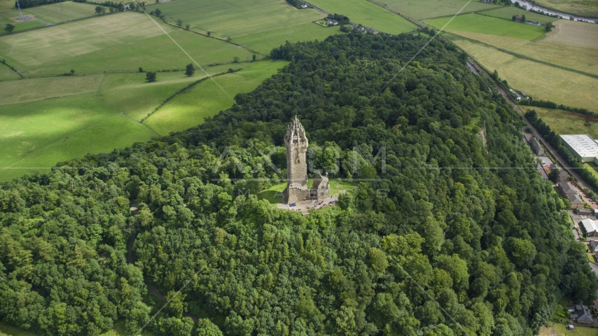 The historic Wallace Monument surrounded by trees on Abbey Craig hill in Stirling, Scotland Aerial Stock Photos | AX109_100.0000008F