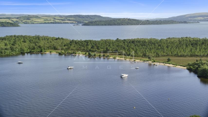 Boats along a small island beach, Loch Lomond, Scottish Highlands, Scotland Aerial Stock Photos | AX110_109.0000158F