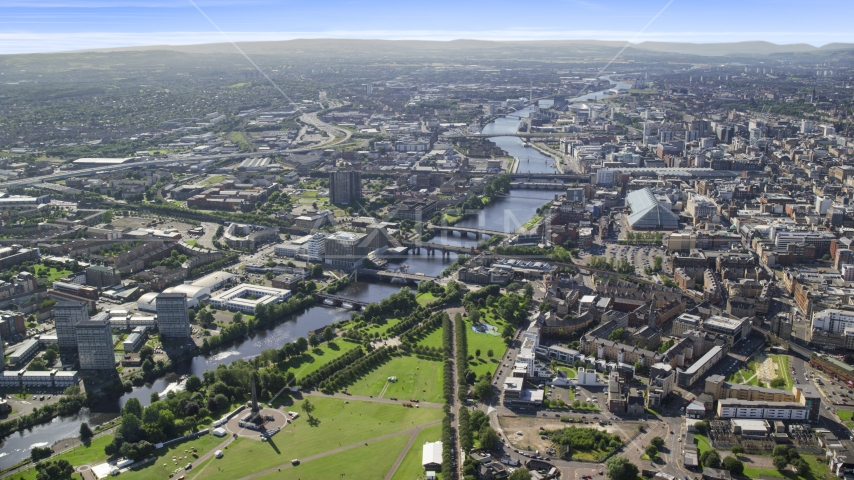 A wide view of River Clyde and bridges near city buildings in Glasgow, Scotland Aerial Stock Photos | AX110_163.0000000F