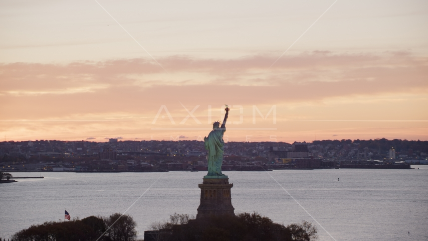 Statue of Liberty with a view of Brooklyn at sunrise, New York Aerial Stock Photos | AX118_041.0000196F
