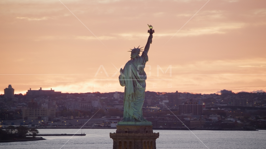 Statue of Liberty with a view of Brooklyn at sunrise, New York Aerial Stock Photos | AX118_042.0000000F