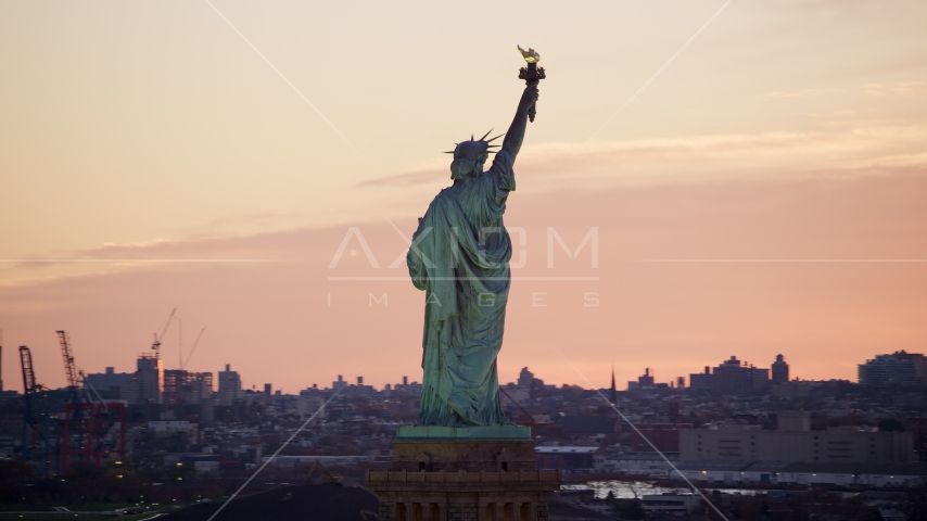 Behind the Statue of Liberty at sunrise, New York Aerial Stock Photos | AX118_042.0000234F