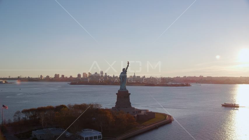 Statue of Liberty and Brooklyn across the harbor at sunrise in New York Aerial Stock Photo AX118_118.0000187F | Axiom Images