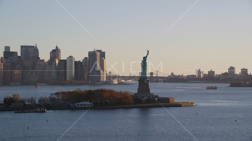 Statue of Liberty and Lower Manhattan skyscrapers at sunrise in New York City Aerial Stock Photos | AX118_132.0000000F