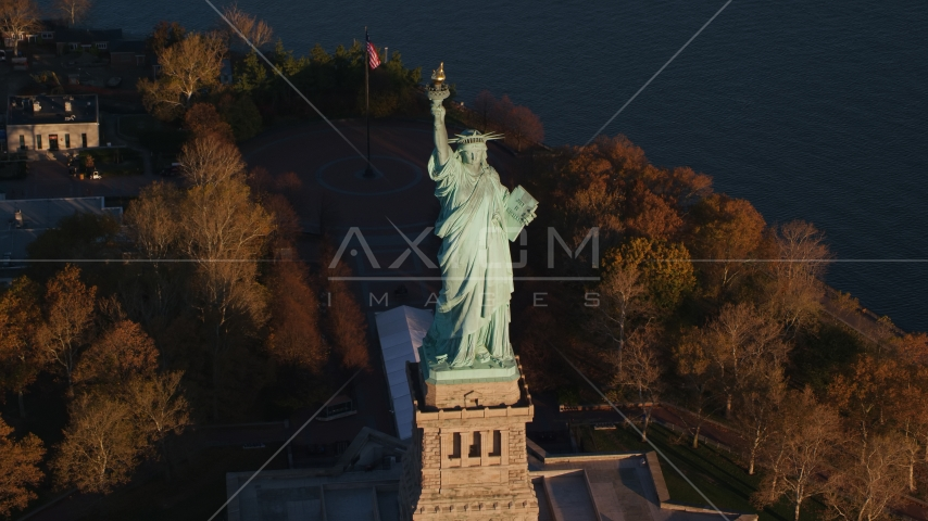 Statue of Liberty and autumn trees at sunrise in New York Aerial Stock Photos | AX118_146.0000077F