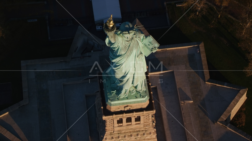Bird's eye view of the Statue of Liberty at sunrise in New York Aerial Stock Photos | AX118_147.0000104F
