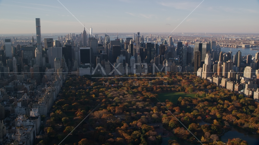 Central Park with autumn leaves and Midtown skyscrapers at sunrise in New York City Aerial Stock Photos | AX118_194.0000000F