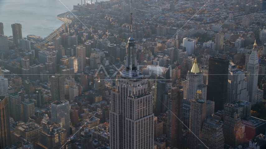 The spire on top of the Empire State Building at sunrise in Midtown Manhattan, New York City Aerial Stock Photos | AX118_204.0000082F