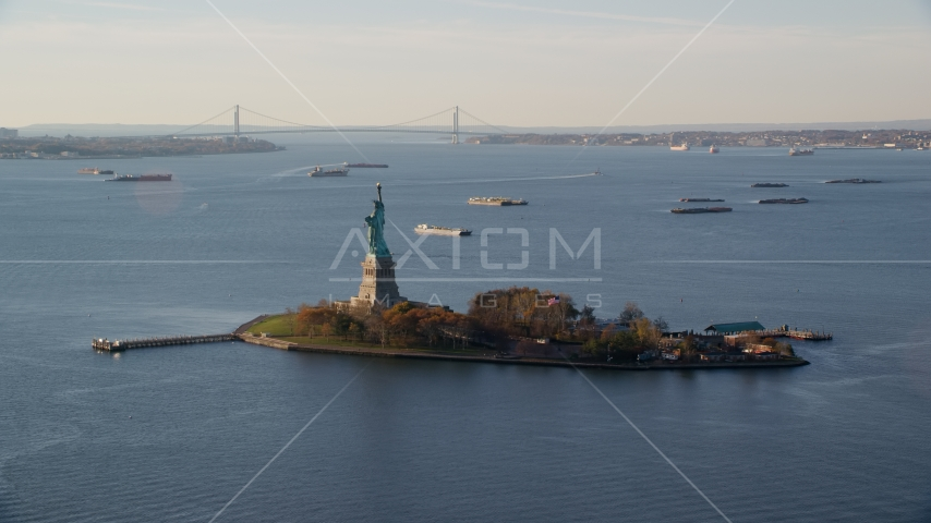 Statue of Liberty and barges in New York Bay at sunrise in New York Aerial Stock Photos | AX118_216.0000172F